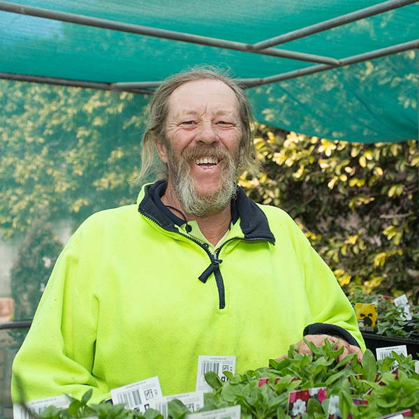 man with long grey beard in bright yellow jumper smiling outside