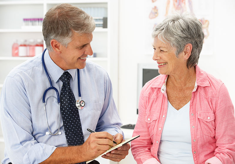 grey haired doctor consulting elderly woman patient
